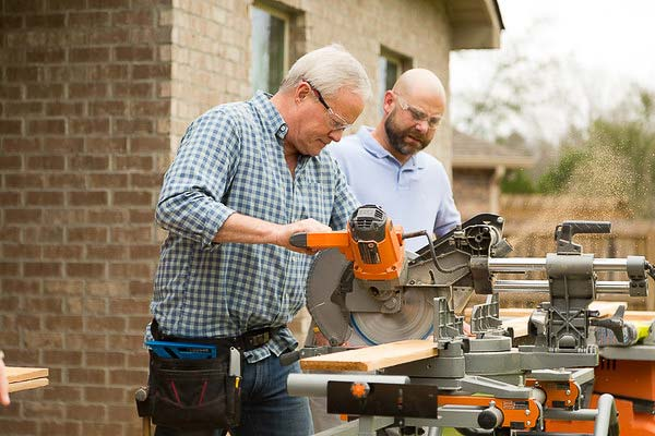 Danny Lipford cuts cedar for a window seat as Rich Jones looks on