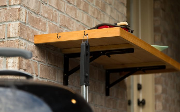 Folding counter near barbecue grill outdoors on a cloudy day