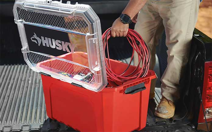 Man placing extension cord in a Husky professional-grade storage tote with clear plastic lid