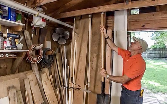 Joe Truini hangs gardening tools on the ceiling joists of his storage shed
