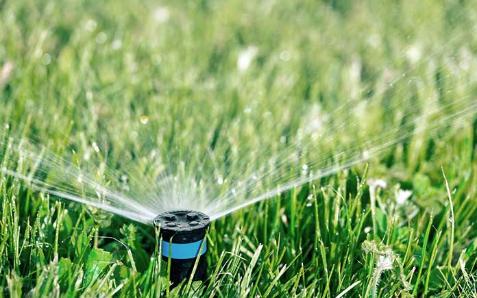 Automatic sprinkler system irrigating lawn