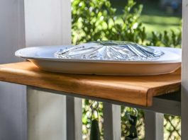 Wooden counter set on a porch railing with a platter on top