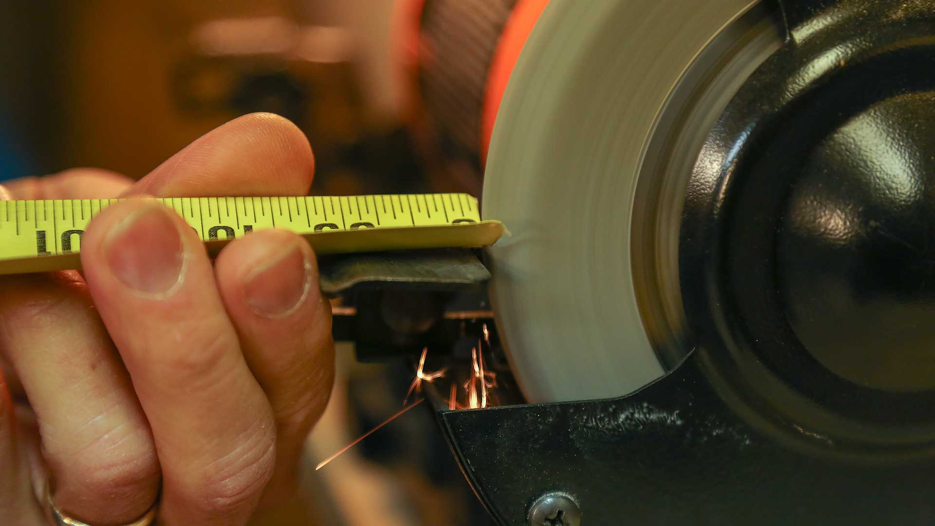 Placing tape measure near bench grinder to work on its edges