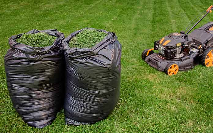 bags of grass clippings beside a lawn mower