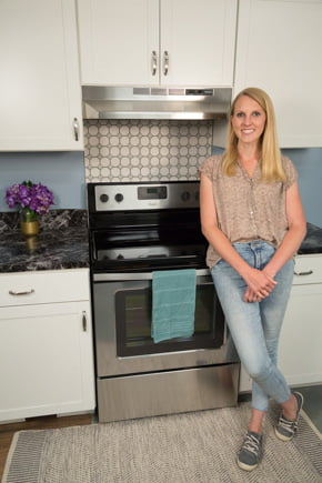 Chelsea Lipford Wolf stands in front of completed tile backsplash in blue kitchen