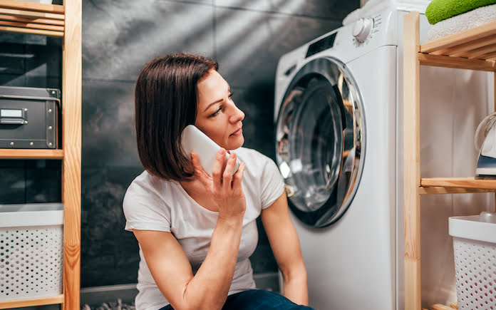 Woman wearing white shirt sitting at laundry room by the washing machine and calling for appliance repair service