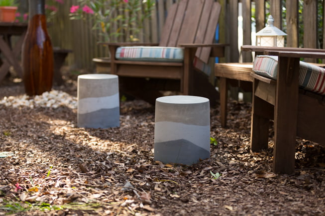 Concrete ottomans on display beside two Adirondack chairs in a backyard