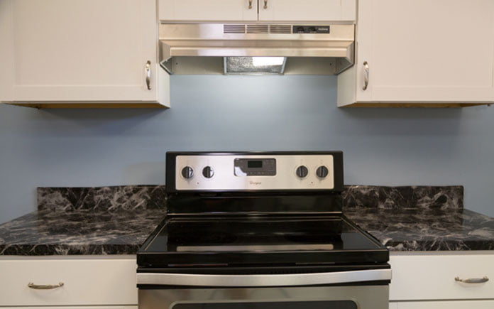 Kitchen with black range, range hood and blue wall and white countertop