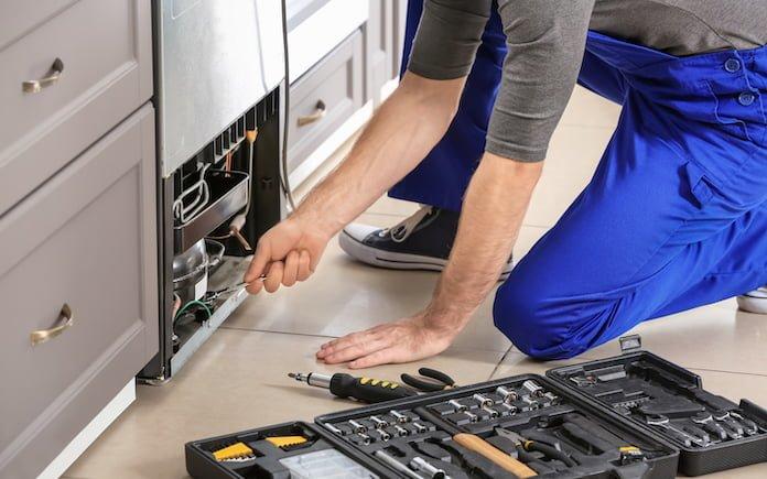Male technician repairing refrigerator indoors