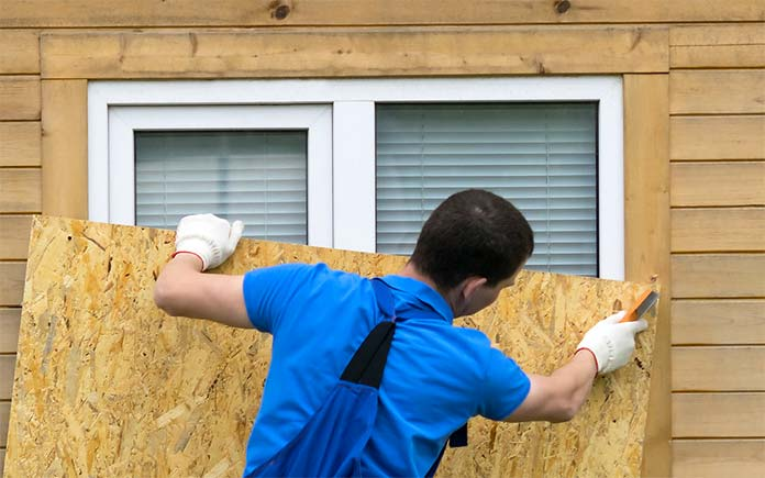 Man prepares for hurricane by covering his windows with plywood panels