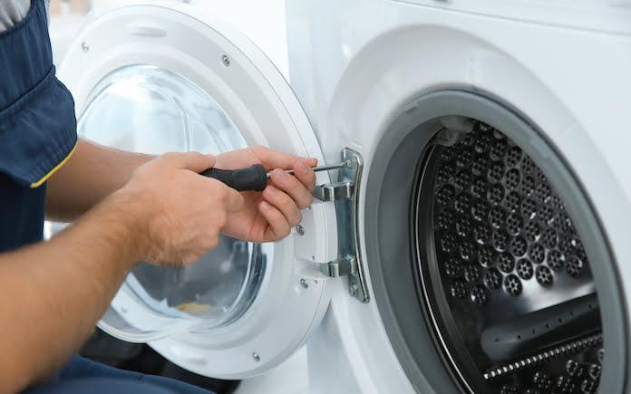 Young plumber fixing washing machine in bathroom, closeup