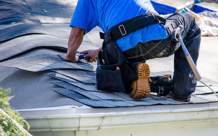 Repairing the roof of a home. A worker replaces shingles on the roof of a home