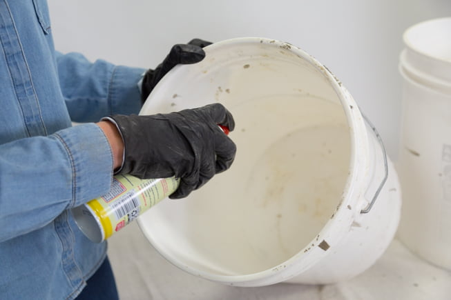 Spraying a plastic bucket with cooking spray