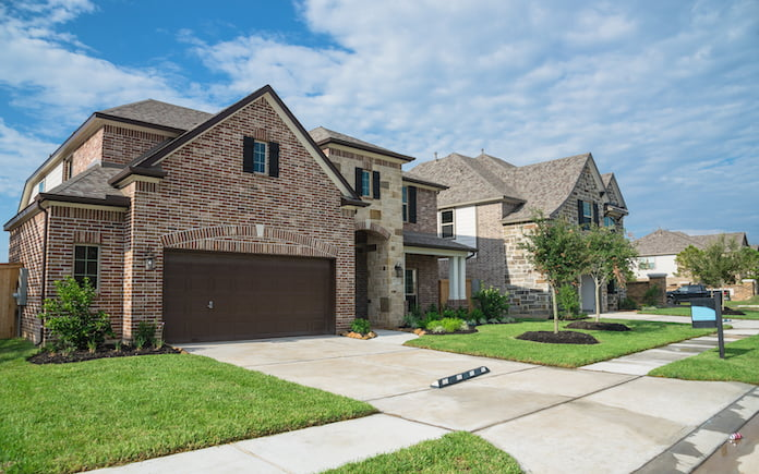 Suburban American neighborhood street with row of brand new two story residential houses in Humble, Texas, US. Newly constructed, freshly built modern home with landscaped yard.