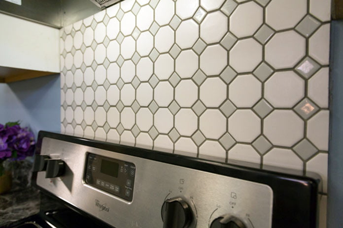 Tile backsplash installed over kitchen range