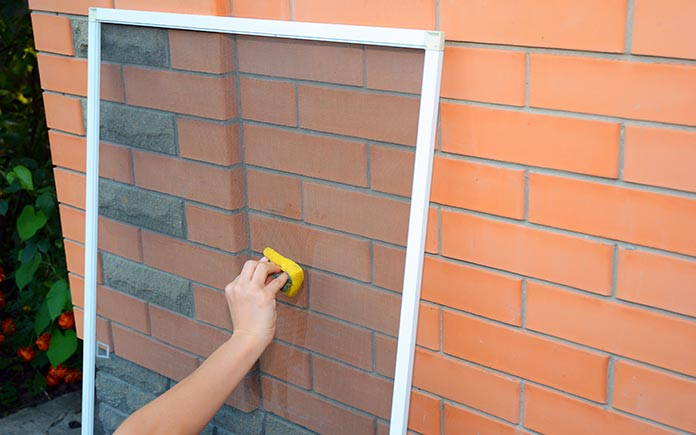 L'homme lave les moustiquaires des fenêtres avec une éponge humide à la main