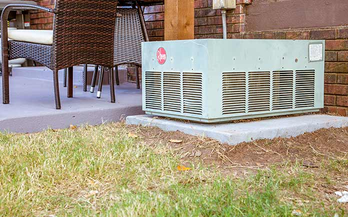 Air conditioner unit resting on a concrete pad