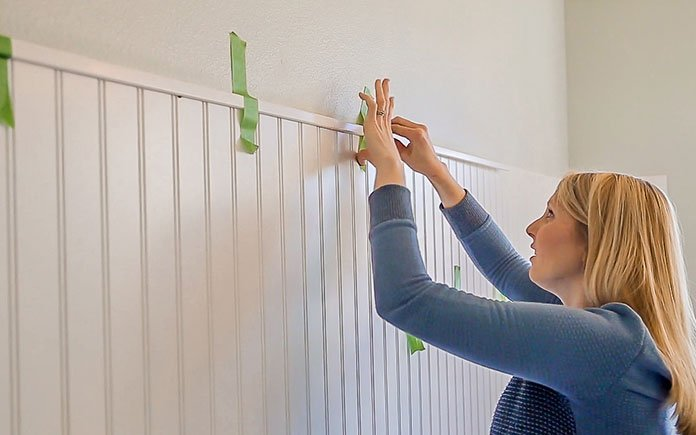 Chelsea Lipford Wolf applies painter's tape to a wall
