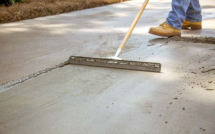 Applying Quikrete Concrete Resurfacer with a squeegee on a concrete slab