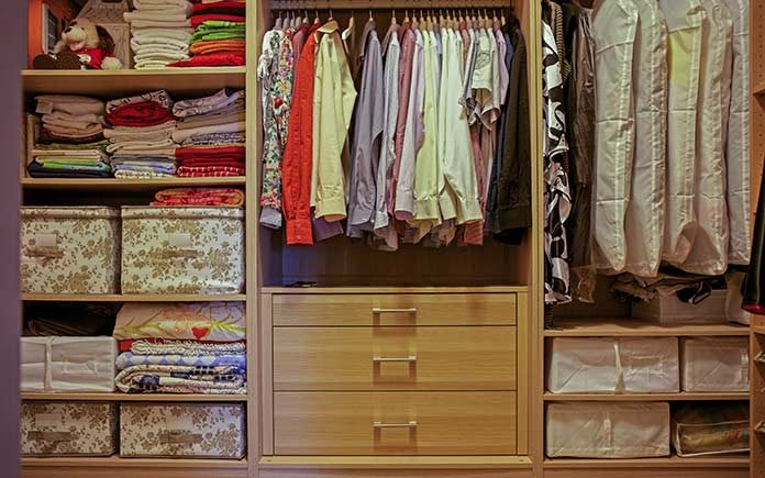 Clothes in designer cloth boxes in closet