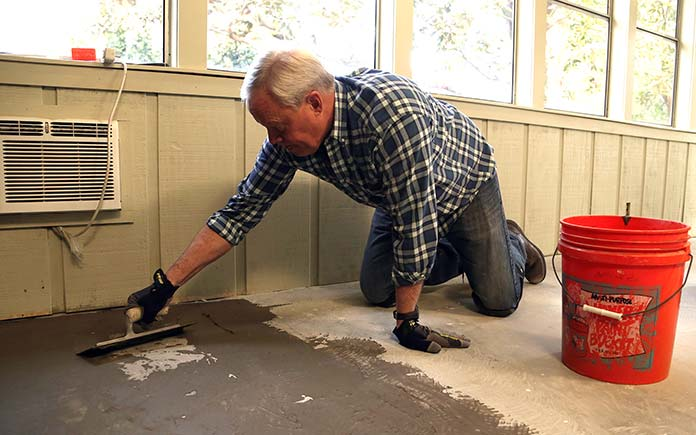 Danny Lipford spreading concrete mix inside a house