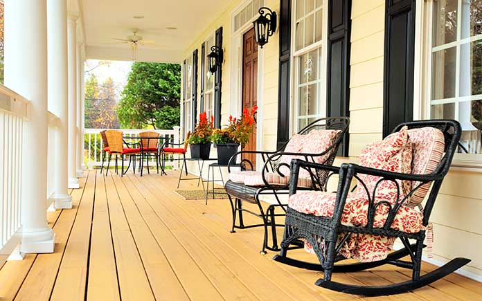 Front porch with rocking chairs, planters and a dining set