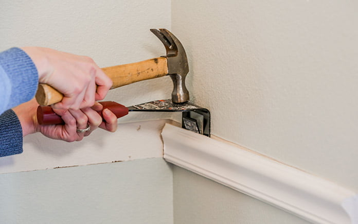 Hammering a trim puller into a wall