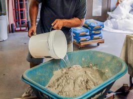 Man pours a bucket of water into the Quikrete countertop concrete mix in a wheelbarrow