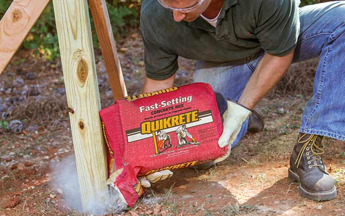 Man pours Quikrete Fast-Setting Concrete Mix into a post hole while building a fence.