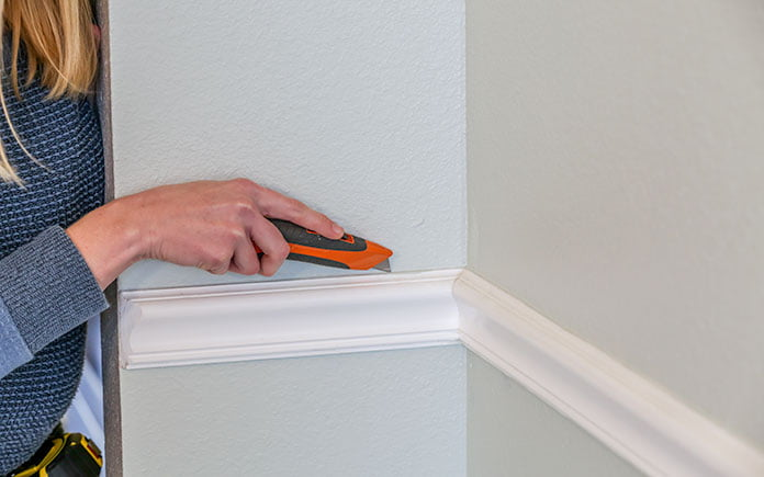 Scoring a chair rail with a utility knife