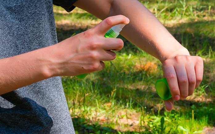 Man holding a spray bottle sprays the skin on his left arm outside
