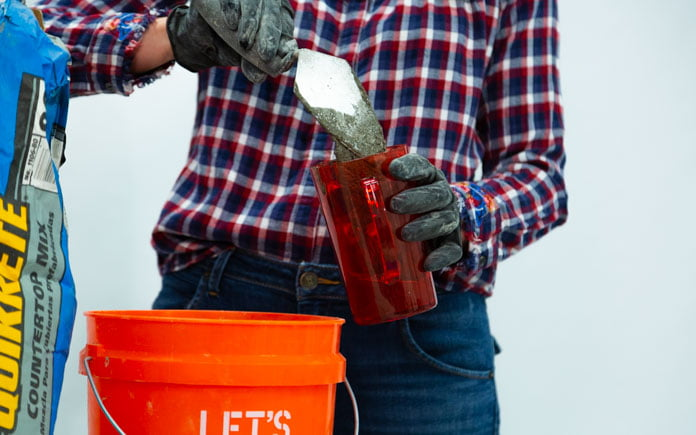 A gloved hand uses a masonry trowel to pour concrete mix into a plastic cup