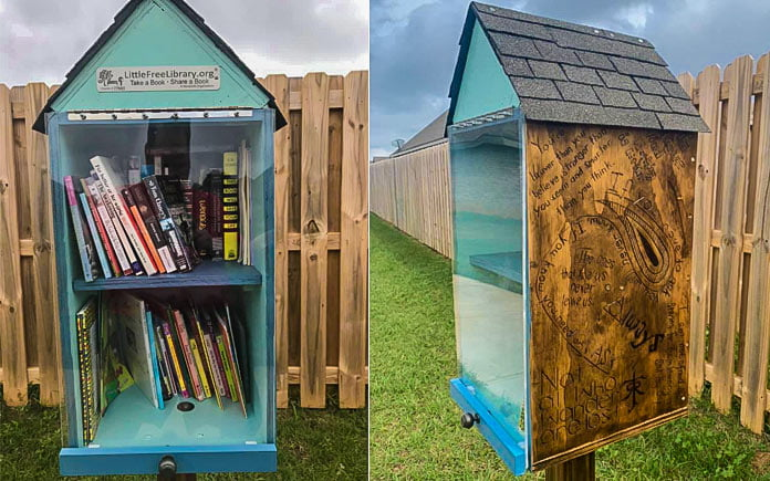 Blue Little Free Library seen in a neighborhood common area in front of a wooden fence