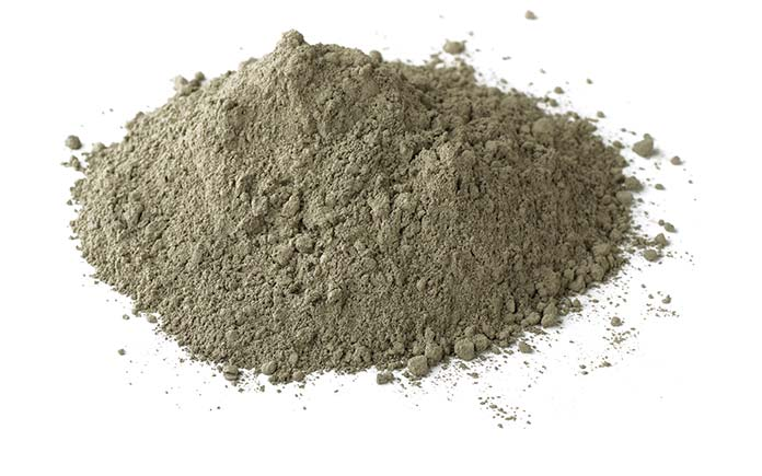 A pile of cement, in powder form, appears with a seamless white background. It will be added to concrete mix later.