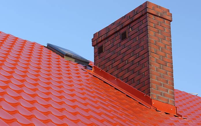 Red flashing surrounding brick chimney on red metal roof