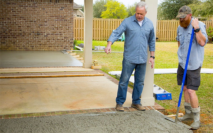 Danny Lipford looks at a wet concrete patio in production at the job site. The cement was premixed with the aggregate materials in the concrete.