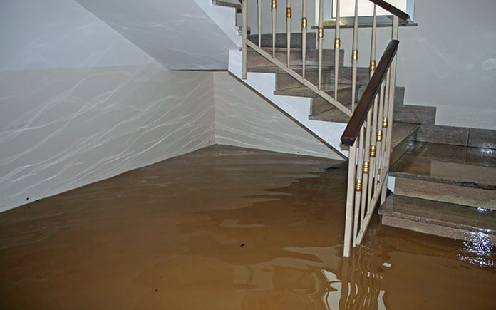 Flooded downstairs in a home, seen from the living room with the staircase in view