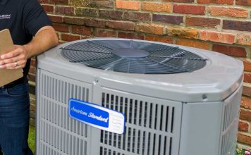 Friendly American Standard HVAC technician, who is wearing a cap, smiles, holds a clipboard, and stands beside a condenser unit