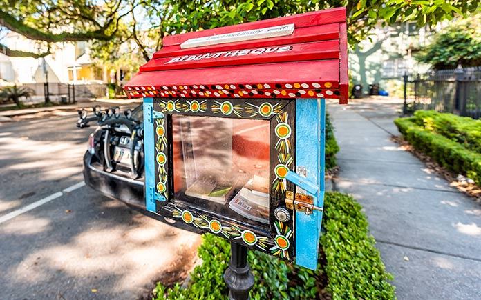 Petite bibliothèque gratuite avec un toit rouge et des côtés bleus dans le Garden District de la Nouvelle-Orléans
