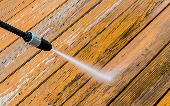 Closeup of a pressure washer shooting out water on a deck during a cleaning.