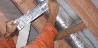 Woman repairs air conditioner ductwork with metallic foil tape