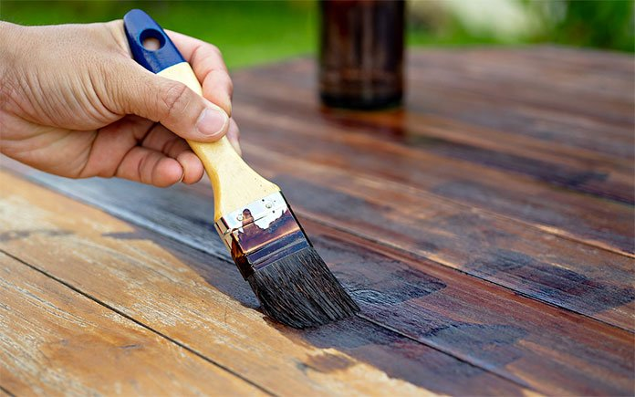 Closeup of a man's hand holding a paintbrush as he stains a wood deck