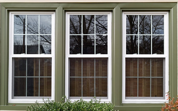 Three vinyl windows, seen close up, reflecting a picturesque neighborhood