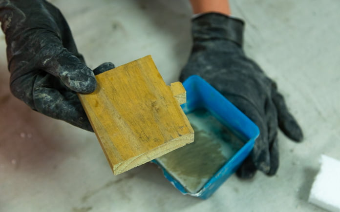 Every home office should be designed with functionality in mind, including a place to rest a smart phone. A gloved hand prepares to place a wood cutout into a plastic concrete form