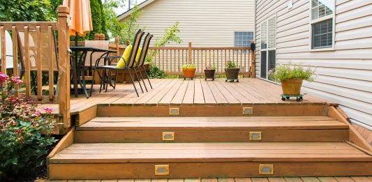 Deck stairs leading up to a townhouse with vinyl siding
