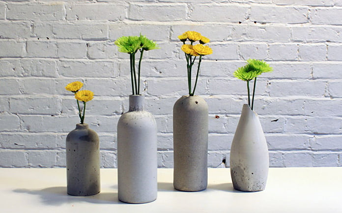 Concrete bottles, seen close up, repurposed as flower vases