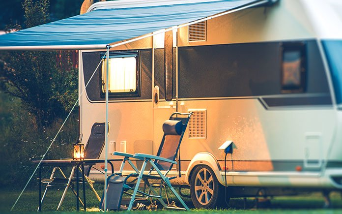 Camper, as seen at night, with the two folding chairs under a pop-out awning