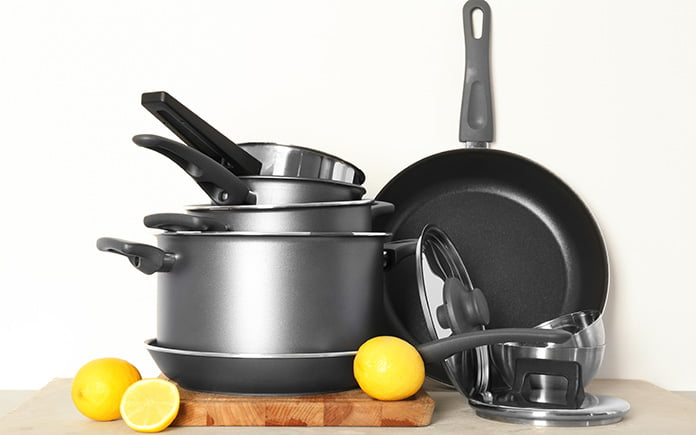 Stacked cookware set with cooking board and lids, ready for storage in a college apartment