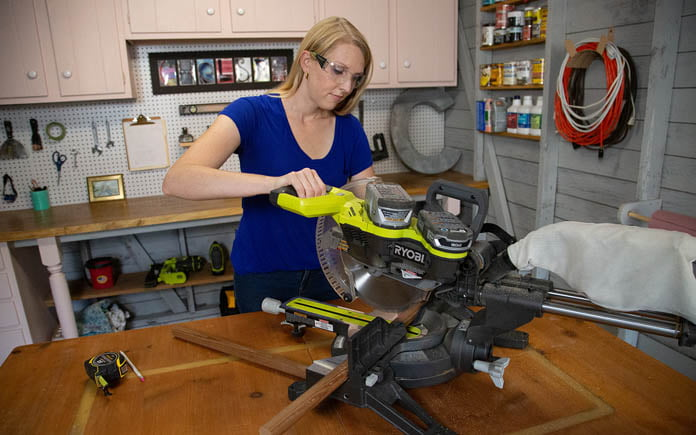 Chelsea Lipford Wolf cuts a wood dowel with her miter saw in her pink workshop