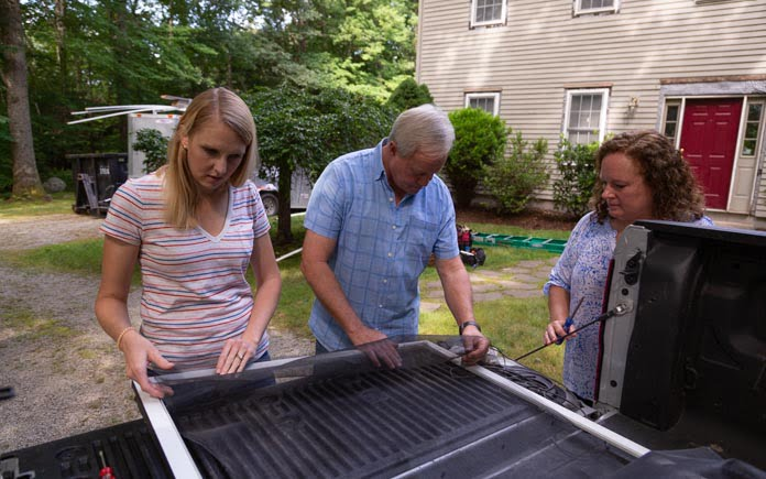 Chelsea Lipford Wolf, Danny Lipford and Merry Beth Cutler of Exeter, Rhode Island, work together to replace a screen from a sliding patio door.